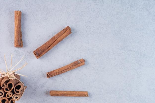Палочки корицы, изолированные на бетонном фоне.