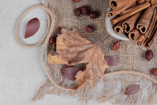 Bastoncini di cannella, foglie e corda su tela. foto di alta qualità