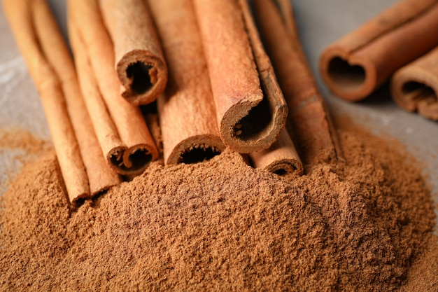 Cinnamon sticks and powder on grey wall, closeup