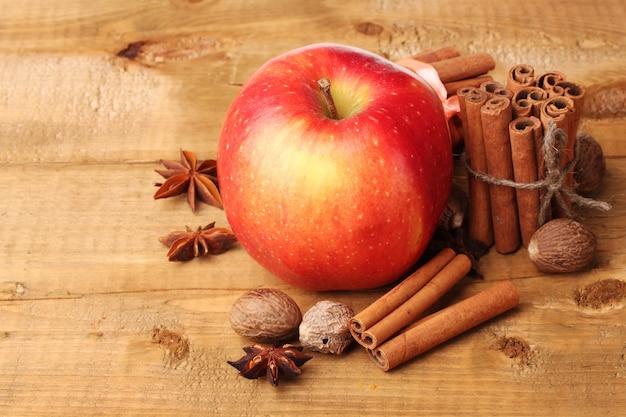 나무 테이블에 계피 스틱, 빨간 사과, 육두구, 아니스
