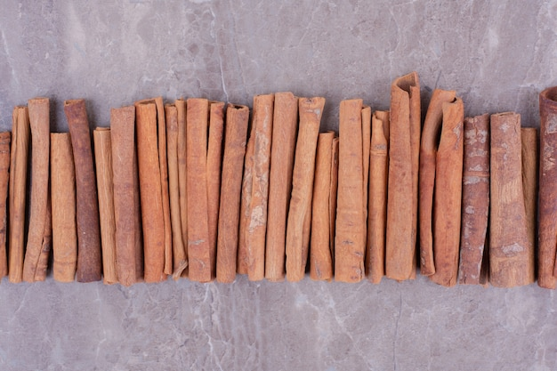 Cinnamon sticks in a row on the stone surface