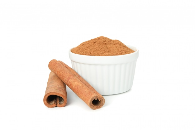 Cinnamon sticks and sauceboat with powder isolated on white wall