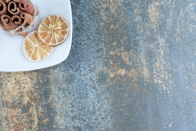 Bastoncini di cannella e limoni a fette sul piatto bianco.