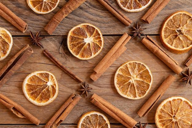 계피 스틱, 말린 오렌지 조각, 나무 배경에 스타 아니스. 평면도. 크리스마스와 새 해 축 하 개념입니다. 패턴 배경입니다.