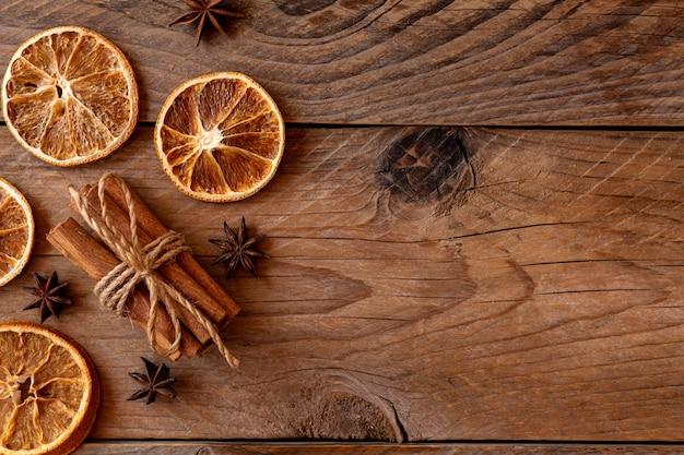 계피 스틱, 말린 오렌지 조각, 복사 공간이 있는 나무 배경에 스타 아니스. 평면도. 크리스마스와 새 해 축 하 개념입니다.