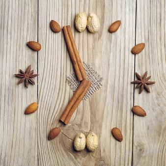 Палочки корицы, бадьян и орехи в виде часов на деревянном столе