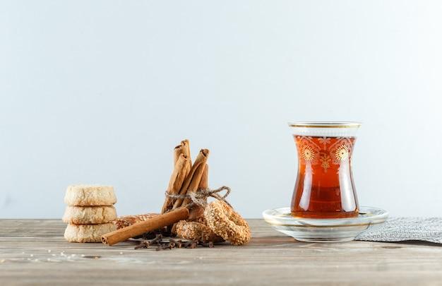 Палочки корицы с печеньем, гвоздикой, стаканом чая, столовыми приборами на деревянной и белой стене