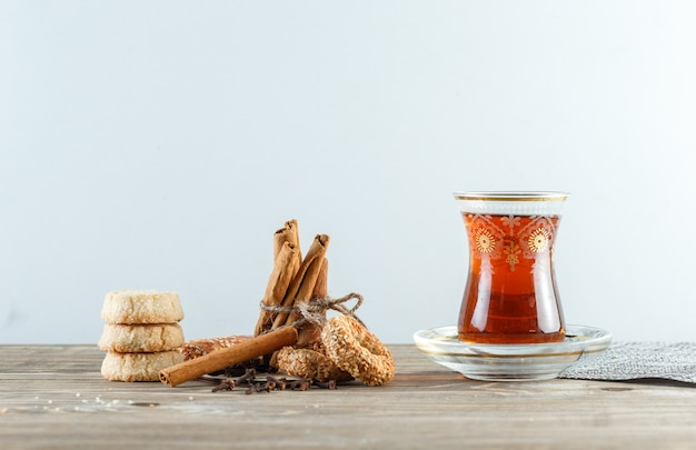 Cinnamon sticks with biscuits, cloves, a glass of tea, placemat side view on wooden and white wall