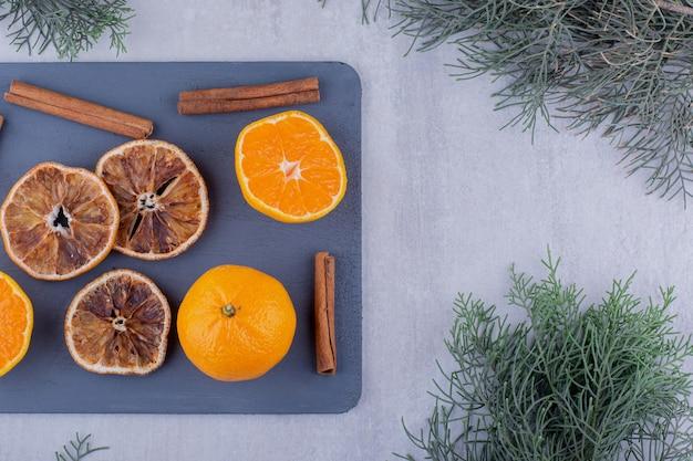 シナモンは、白い背景のまな板にジューシーなオレンジと乾燥したスライスで固執します。高品質の写真