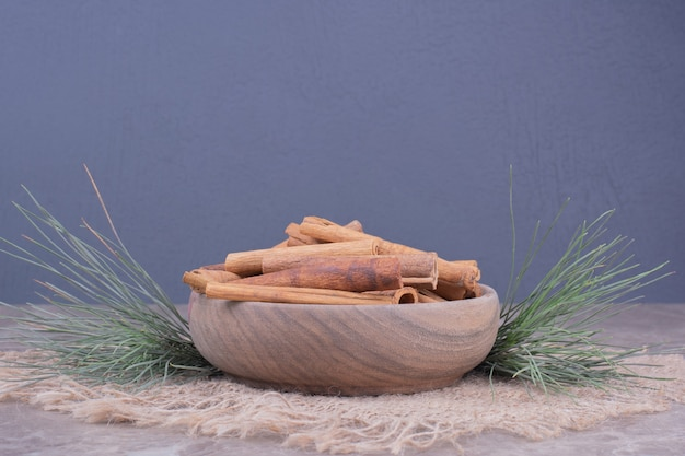 Cinnamon sticks in a wooden cup with oak tree branch around