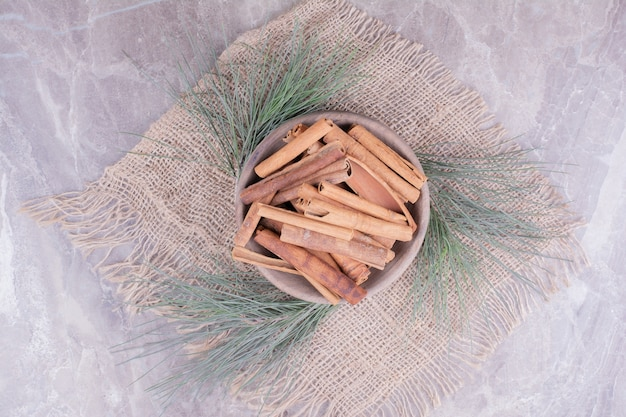 Cinnamon sticks in a wooden cup with oak tree branches around.