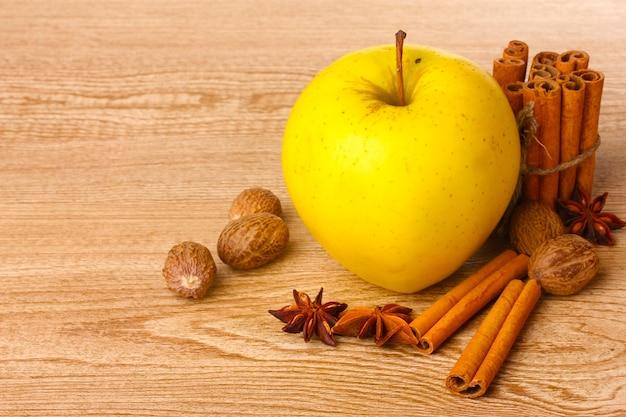 木製のテーブルにシナモンスティック、黄色いリンゴ、ナツメグ、アニス