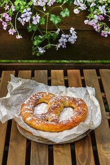 Cinnamon sugar soft pretzel on a wooden table in a street cafe, snack for tea or coffee