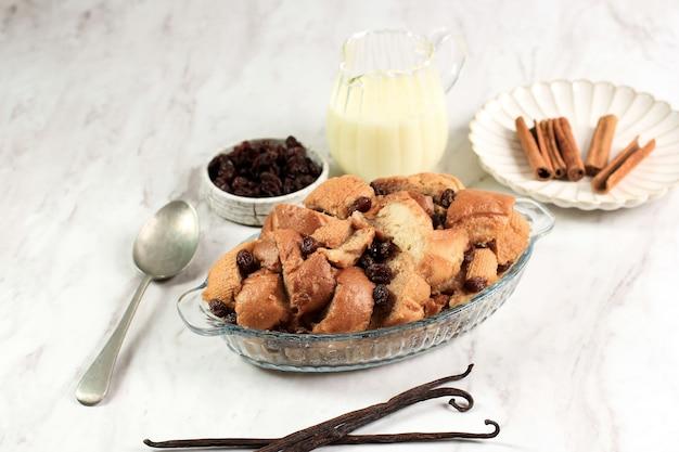 Хлеб с корицей, ваниль и сливочный пудинг с изюмом в прозрачной форме для выпечки, подается с вла. копировать пространство для текста