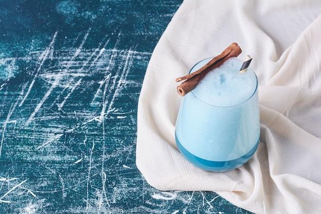 Cannella con una tazza di bevanda sul blu.