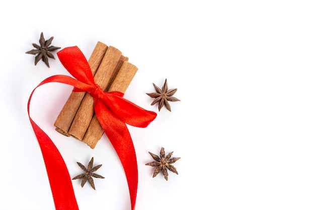 Cinnamon with red bow and star anise on a white . christmas mood. copysapce.