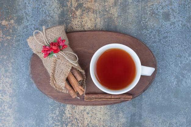 黄麻布のシナモンと木の板のお茶のカップ。高品質の写真