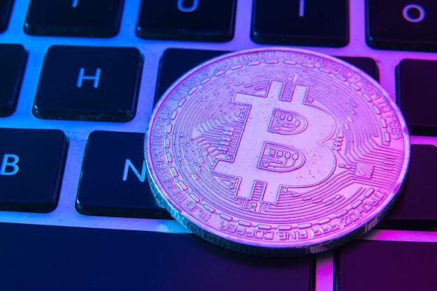 Обведите биткойн-монету поверх кнопок клавиатуры компьютера.