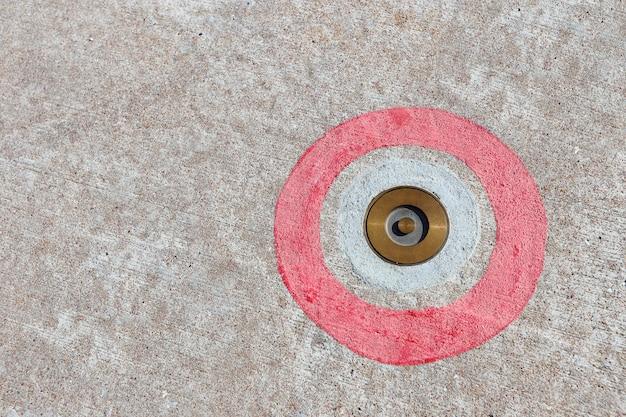 Круглая латунная красная краска на твердом бетонном полу, успешная бизнес-цель