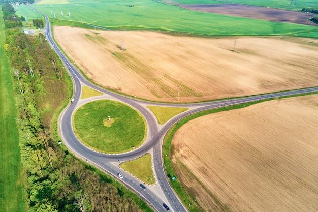 Круговой перекресток среди полей в сельской местности, транспортная инфраструктура с высоты птичьего полета Premium Фотографии