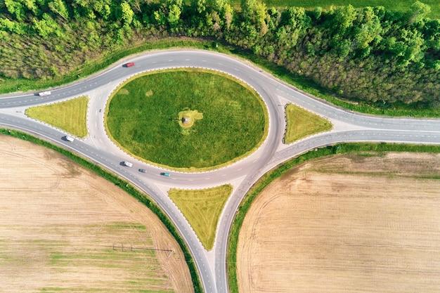 Круговой перекресток среди полей в сельской местности, транспортная инфраструктура с высоты птичьего полета