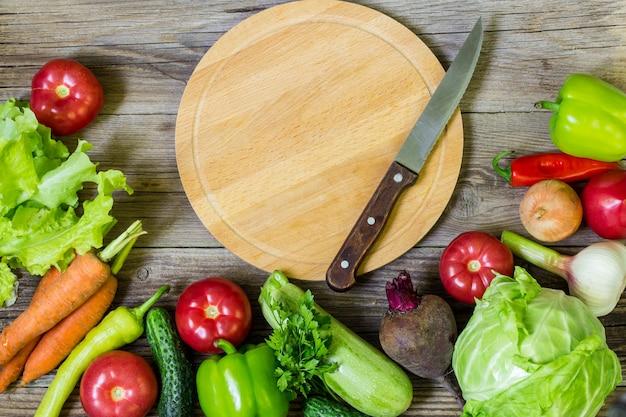 Разделочная доска круга и овощи на деревянных фоне. здоровое питание