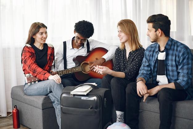 Circolo di amici diversi riuniti a casa. un ragazzo canta mentre suona la chitarra.