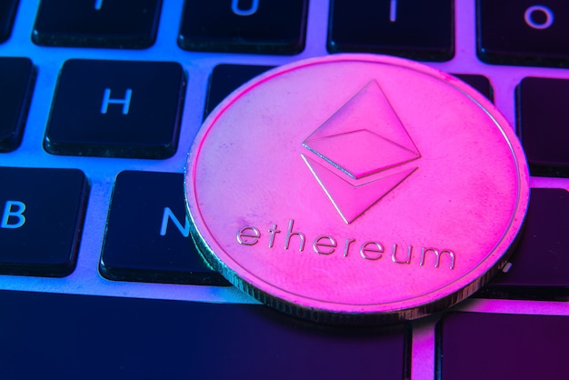 Circle ethereum coin on top of computer keyboard buttons.