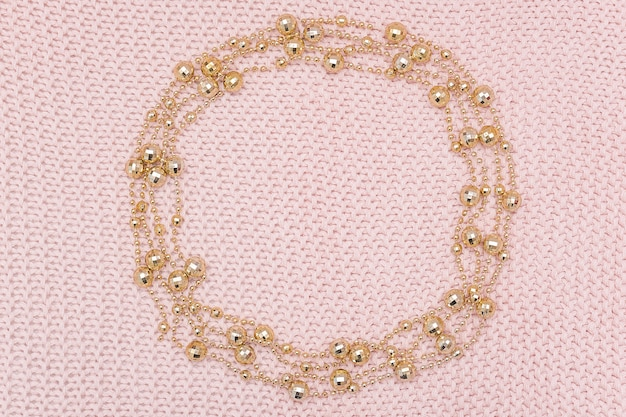 Circle frame from golden beads garland on knitted pink background.