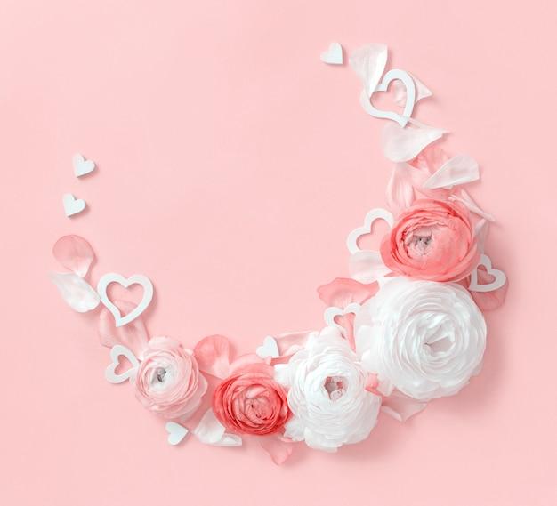 Круглая рамка из цветов, лепестков и сердечек ранункулюсов на светло-розовом виде сверху