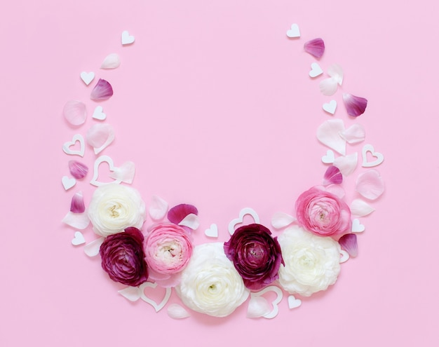 Circle frame made of ranunculus flowers, petals and hearts on a light pink top view