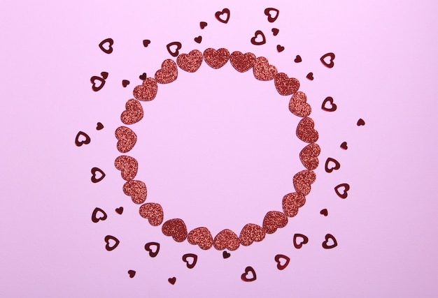 Circle frame of red glitter hearts on pink background. romantic, st valentines day concept.top view.