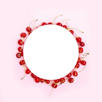Circle frame of red ripe cherries with green mint leaves on a pink background