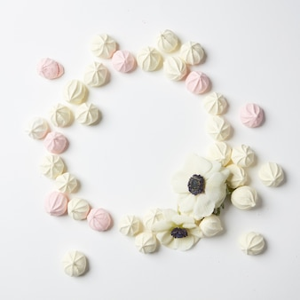 Circle of handmade sweet pink and white zephyr marshmallow. heart small candies over white background.