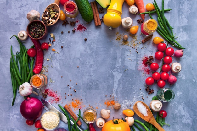 Circle of healthy colorful spicy flavoured seasoning with fresh summer organic antioxidant fruits and vegetables for vegan or vegetarian recipes isolated on grey background. healthy lifestyle concept