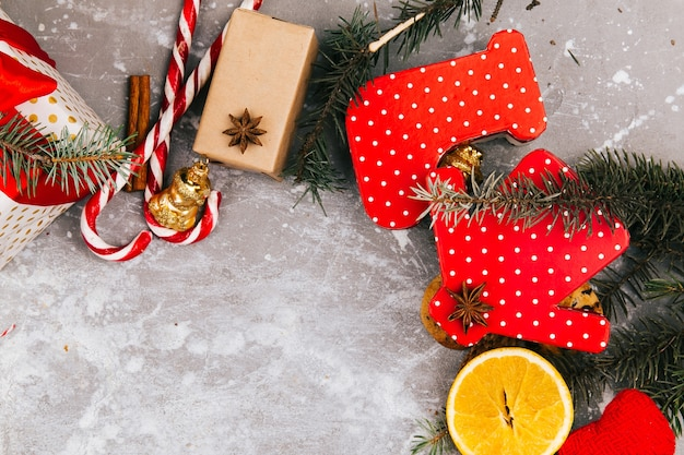 Circle made of oranges, cookies, fir branches, red present boxes and other kinds of christmas decor