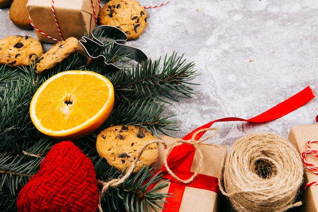 Circle made of oranges, cookies, fir branches and red present boxes