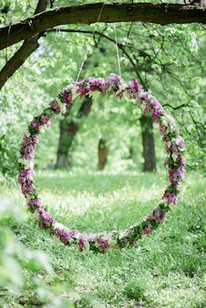Circle made of violet and white lilac hangs from the tree