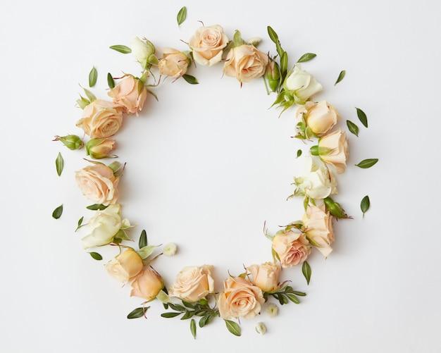 Круг красивых роз с маленькими зелеными листьями на белом фоне.
