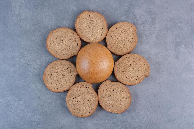 대리석 배경에 단일 롤빵 주위에 갈색 빵 조각의 원. 고품질 사진
