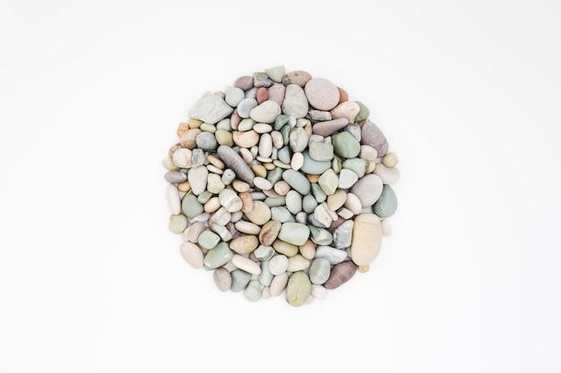 흰색 표면에 다채로운 바다 자갈의 원