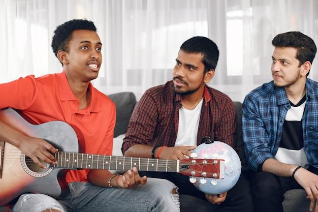 家に集まった多彩なフリンドたち。ギターを弾きながら歌う一人の男。