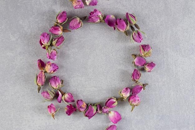 말린 장미 꽃 봉오리의 원은 돌 배경에 놓여 있습니다.