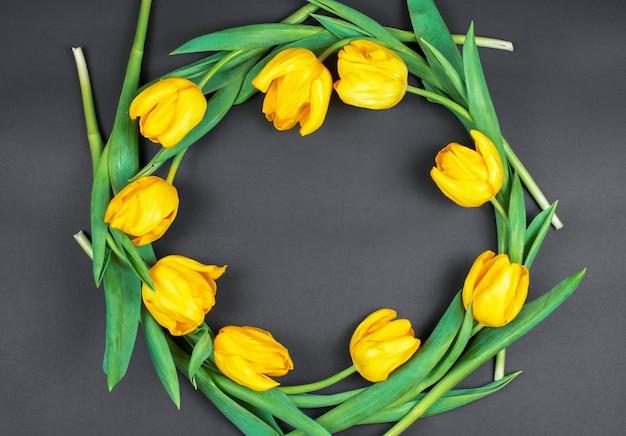 Круг из желтых тюльпанов на черном фоне. место для текста