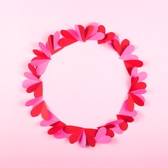 Circle of paper hearts on a pink background for valentine's day.