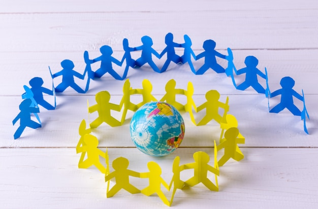 Circle of paper people holding hands around the globe made of paper cut