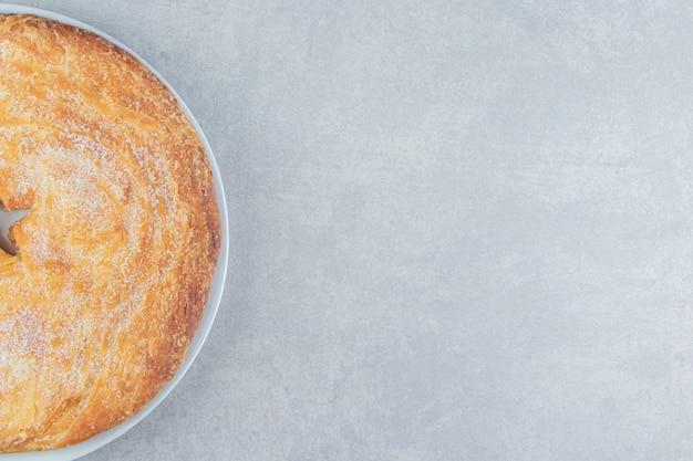 하얀 접시에 가루로 장식된 원형 페이스트리.