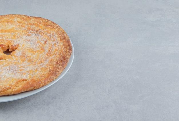 白い皿に粉で飾られたサークルペストリー。