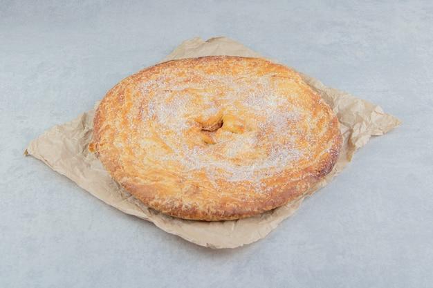 Pasta circolare decorata con polvere bianca su foglio.