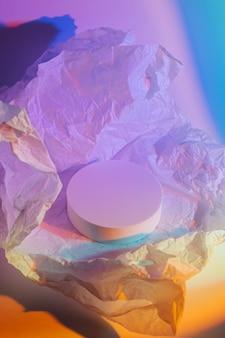 ネオンの光の中でしわくちゃの紙で表彰台を囲みます。製品を表示するスタイリッシュな幾何学的形状。抽象的な背景